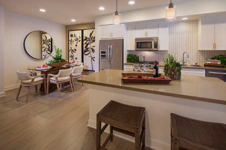 Interior view of dining room and kitchen at Malibu - Villas Playa Vista Apartment Homes in Los Angeles, CA.