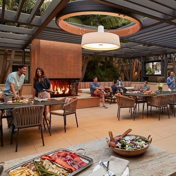 Exterior view of people gathered at outdoor patio at Villas at Playa Vista Apartment Homes in Playa Vista, CA.