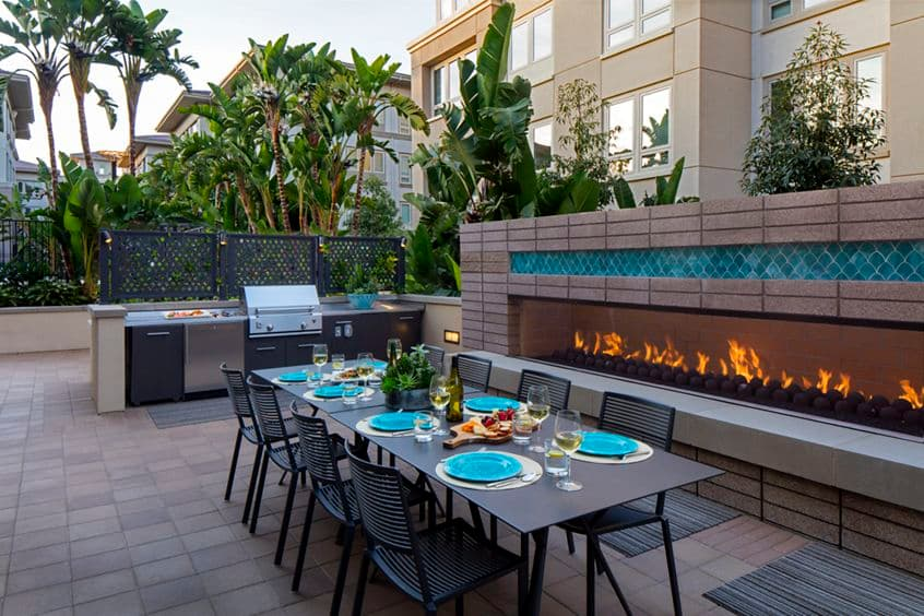 Exterior view of grill area, outdoor patio, and fireplace at Sausalito - Villas at Playa Vista Apartment Homes in Los Angeles, CA.