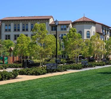 View of building exterior and playground at River Oaks Park at Crescent Village Apartment Homes in San Jose, CA.