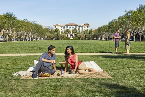Exterior view of people spending time at outdoor lawn at North Park Apartment Homes in San Jose, CA.