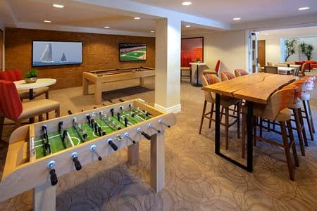 Interior view of game room with foosball table at The Cypress at North Park Apartment Homes in San Jose, CA.