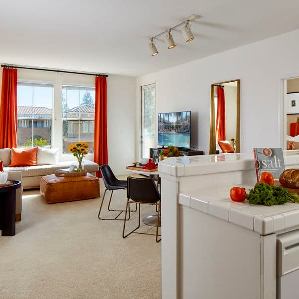 Interior view of a kitchen, dining area, and living room at The Laurels at North Park Apartment Homes in San Jose, CA.