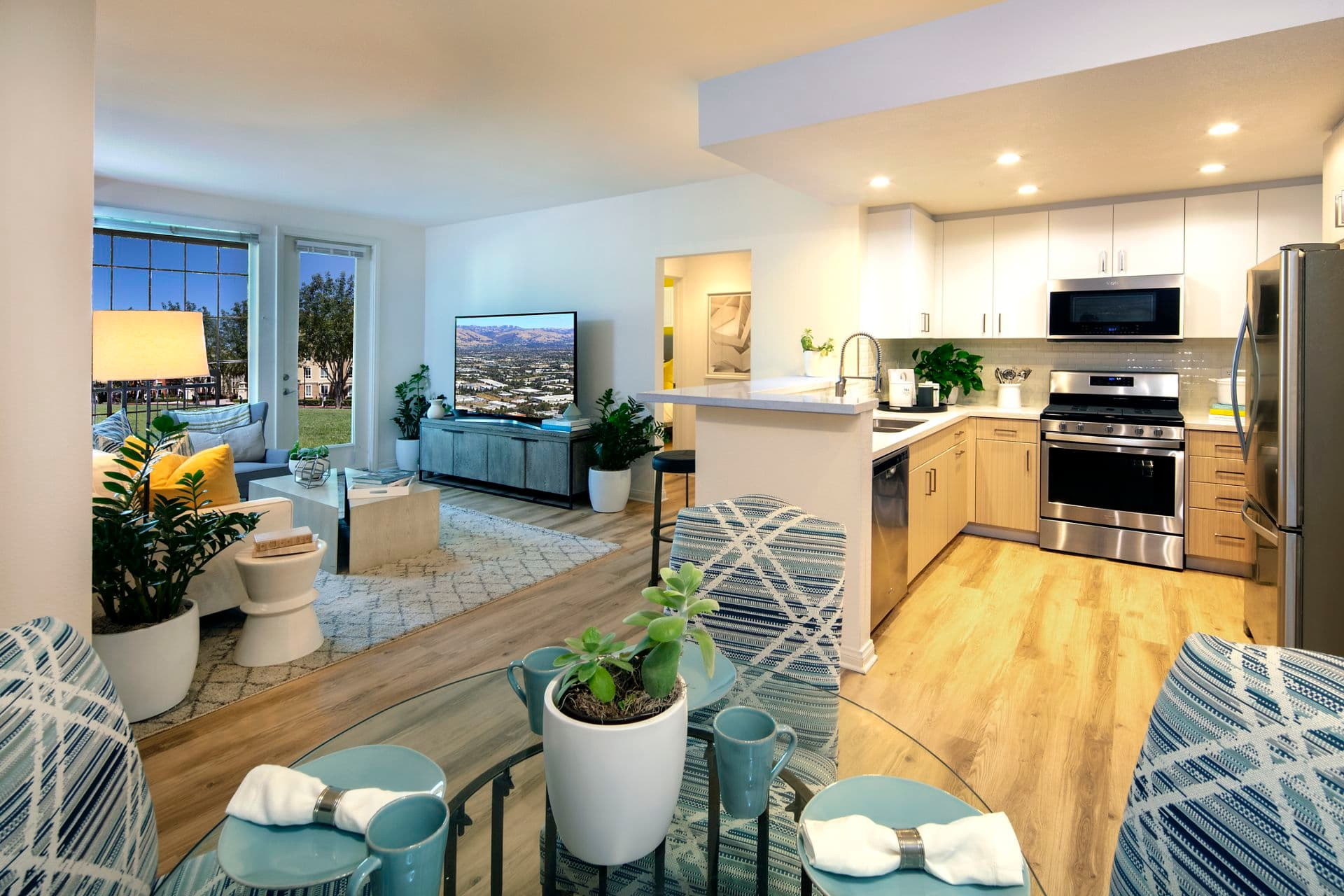 Interior view of a living room and kitchen at The Pines at North Park Apartment Homes in San Jose, CA.