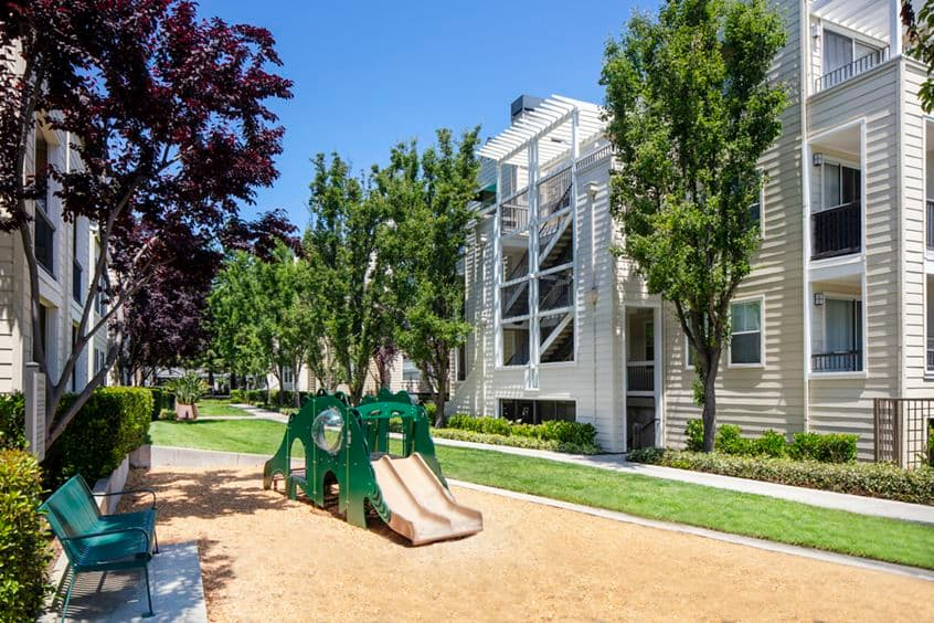 Exterior view of a kid's play area and park at The Hamptons Apartment Homes in Cupertino, CA.
