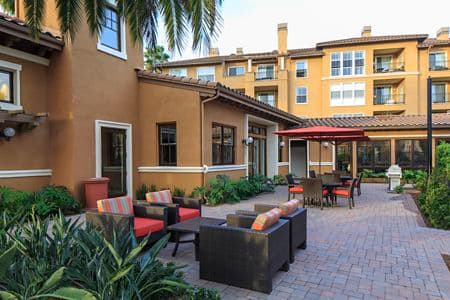 Exterior view of a patio area and lounge seating at The Villas at Bair Island apartment homes in Redwood City, CA.