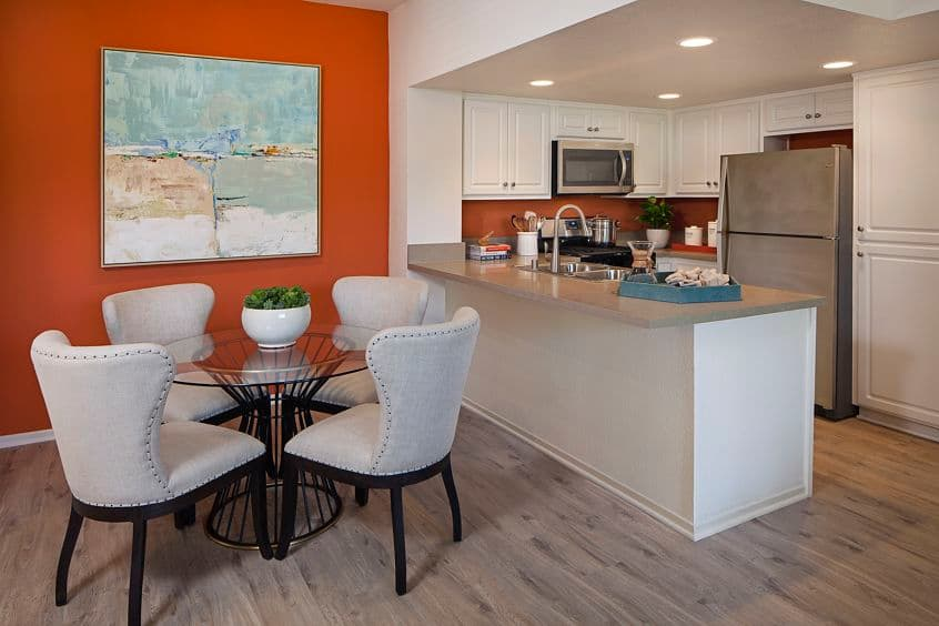 Interior view of dining area and kitchen at Aliso Town Center Apartment Homes in Aliso Viejo, CA.