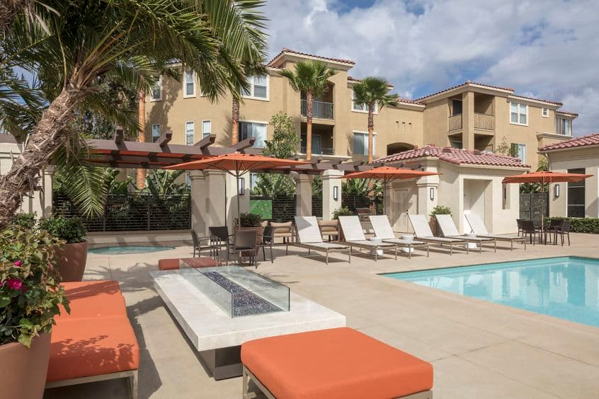 Exterior view of a pool and fire pit at Vista Bella Apartment Homes in Aliso Viejo, CA.