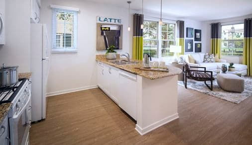 Interior view of living room and kitchen at The Enclave Apartment Homes in Costa Mesa.