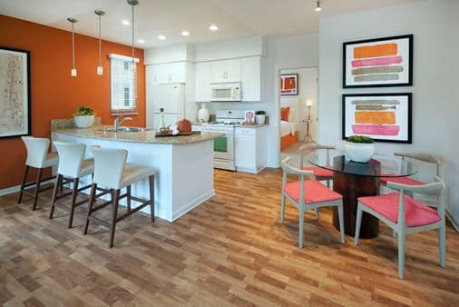 Interior view of dining room and kitchen at The Enclave Apartment Homes in Costa Mesa, CA.