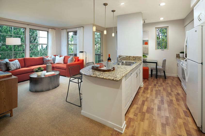 Interior view of living room and kitchen at The Enclave Apartment Homes in Costa Mesa, CA.