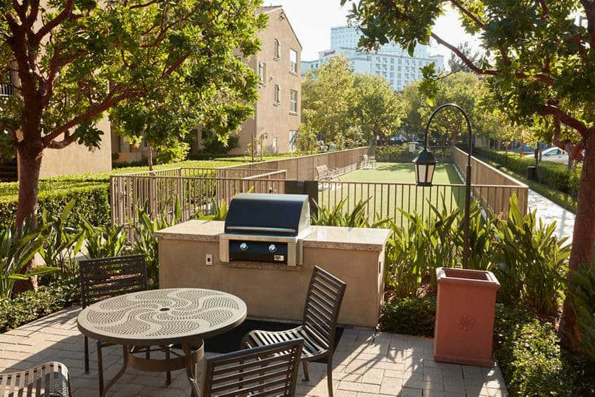 Exterior view of barbecue area and dog park at The Enclave at South Coast Apartment Homes in Costa Mesa, CA.