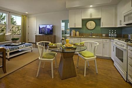 Interior view of living room and kitchen at Umbria Apartment Homes at Cypress Village in Irvine, CA.