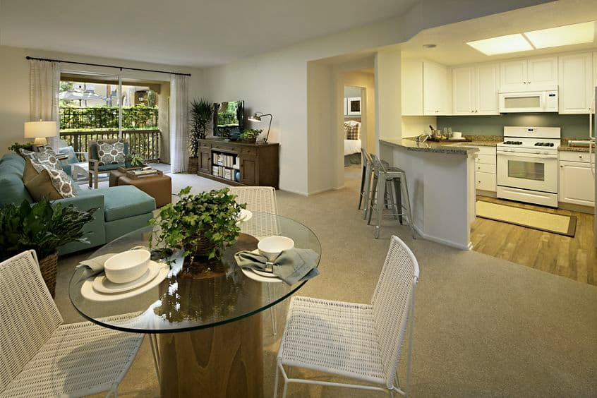 Interior view of dining room, kitchen, and living room at Estancia Apartment Homes in Irvine, CA.