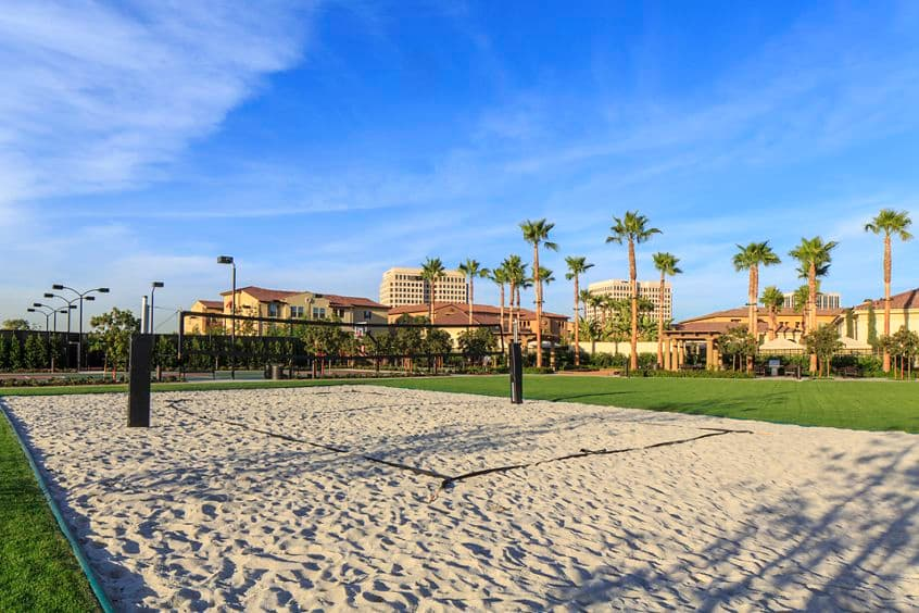 Exterior view of sand volleyball court at Los Olivos Apartment Homes at Irvine Spectrum in Irvine, CA.