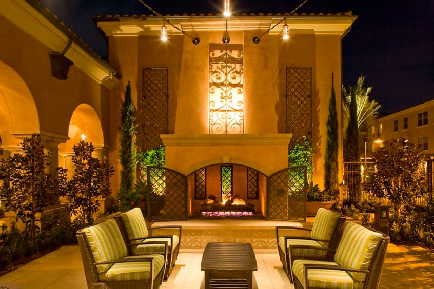 Exterior view of courtyard with a fireplace at Palmeras Apartment Homes in Stonegate, Irvine, CA.