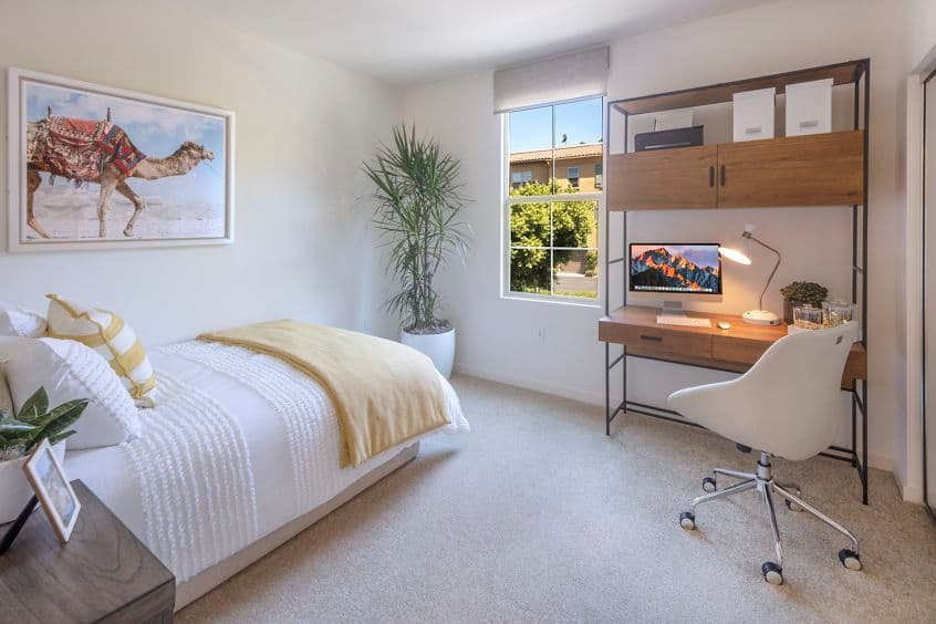 Interior view of bedroom with work space at Palmeras Apartment Home in Irvine, CA.