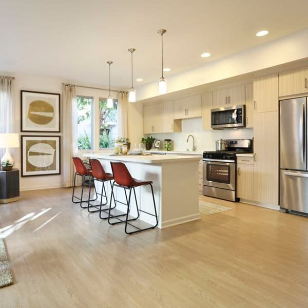 Interior view of kitchen and living room at Park Place Apartment Homes in Irvine, CA.