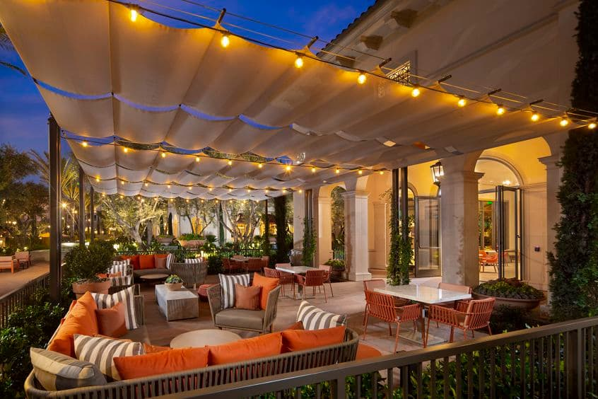 Exterior evening view of Cafe & Market at Promenade Apartment Homes in Irvine, CA.