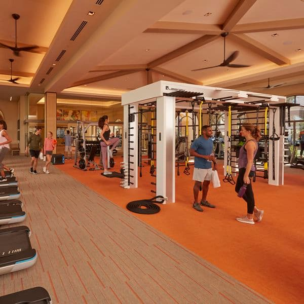 Interior view of people exercising at fitness center at Promenade Apartment Homes in Irvine, CA.
