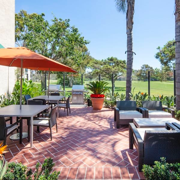 Exterior view of patio and outdoor BBQ at Rancho San Joaquin Apartment Homes in Irvine, CA.