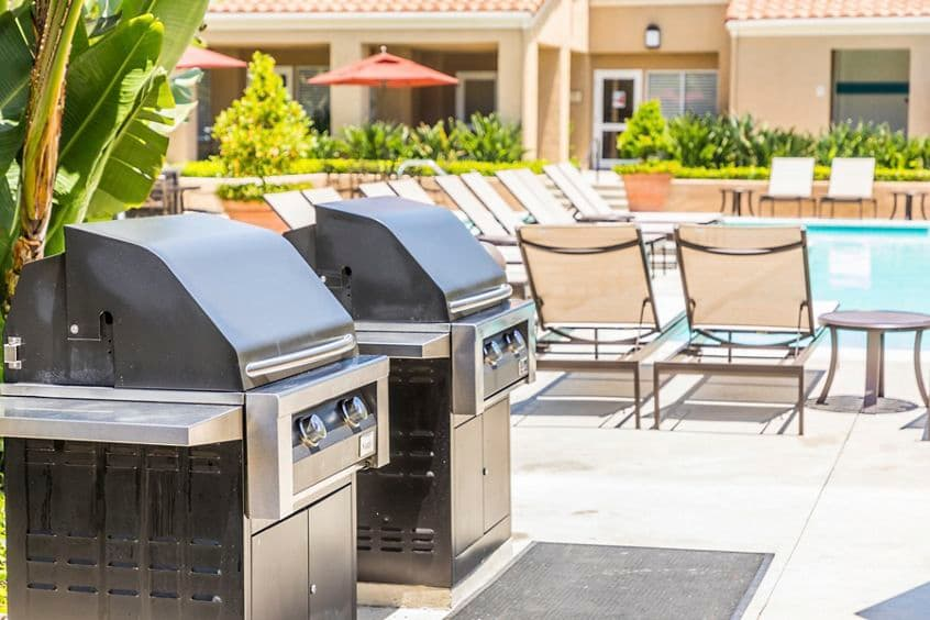 Exterior view of outdoor BBQ area at San Remo Villa Apartment Homes in Irvine, CA.