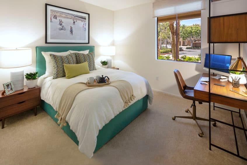 Interior view of bedroom with workstation at Ambrose Apartment Homes at University Town Center in Irvine, CA.