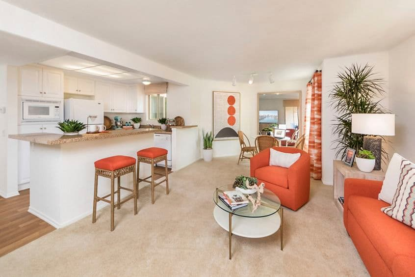 Interior view of kitchen and living room at Dartmouth Court Apartment Homes at Town Center in Irvine, CA.