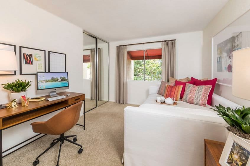 Interior view of bedroom with workstation at Harvard Court Apartment Homes at University Town Center in Irvine, CA.