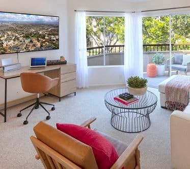 Interior view of living room with workstation at Harvard Court Apartment Homes at University Town Center in Irvine, CA.