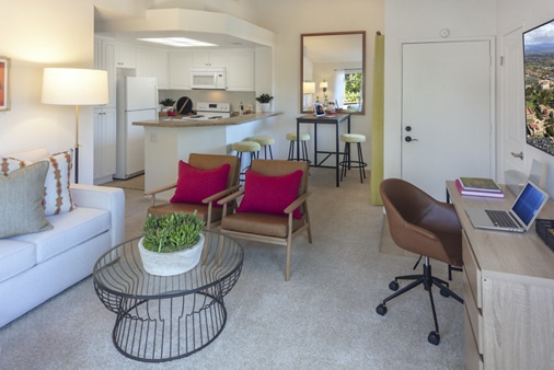 Interior view of kitchen, dining room and living room with workstation at Harvard Court Apartment Homes at University Town Center in Irvine, CA.
