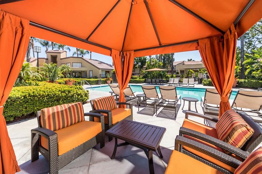 Exterior view of patio near pool at Stanford Court Apartment Homes at University Town Center in Irvine, CA.