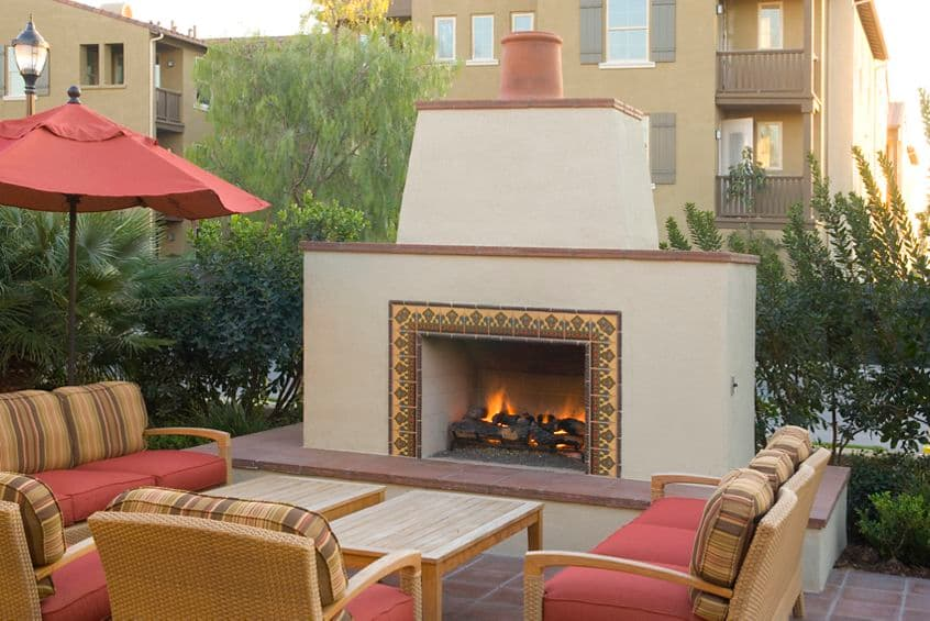 Exterior view of outdoor fireplace at Woodbury Court Apartment Homes in Irvine, CA.