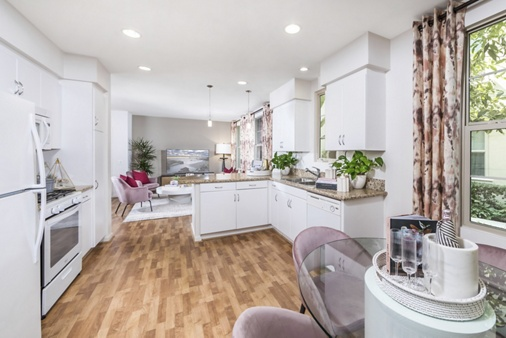 Interior view of the kitchen and living area at Woodbury Court Apartment Homes in Irvine, CA.