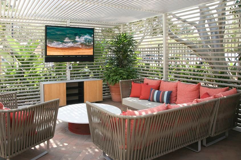 Exterior view of outdoor seating with TV at Baypointe Apartment Homes in Newport Beach, CA.