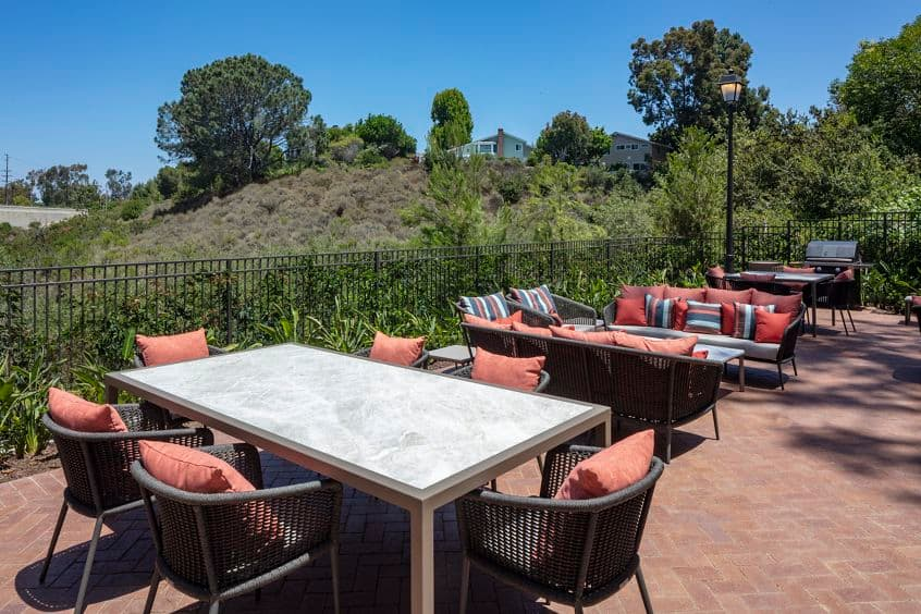 Exterior view of outdoor seating with BBQ at Baywood Apartment Homes in Newport Beach, CA.