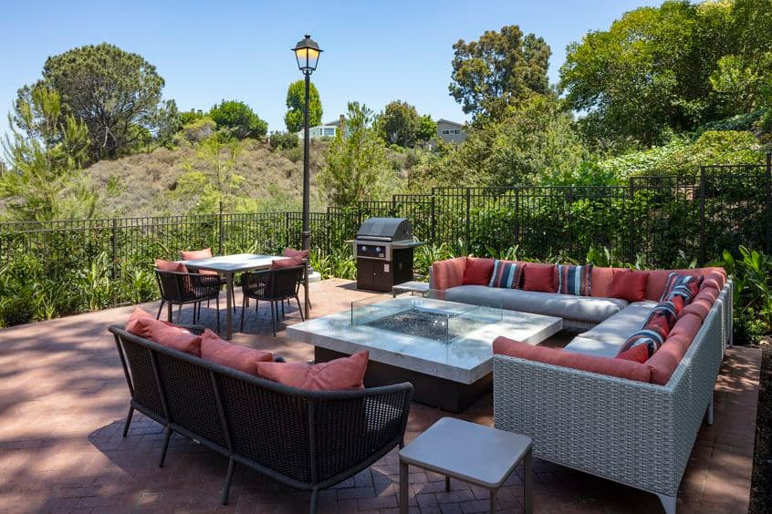 Exterior view of courtyard seating with fireplace at Baywood Apartment Homes in Newport Beach, CA.