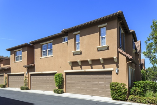 View of building exterior and garage at Bordeaux Apartment Homes in Newport Beach, CA.