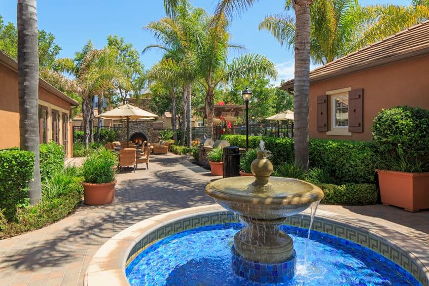 View of building exterior and fountain at Bordeaux Apartment Homes in Newport Beach, CA.