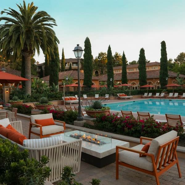 Exterior view of pool and courtyard with fireplace at Newport Bluffs Apartment Homes in Newport Beach, CA.