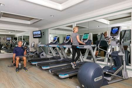 Two people exercising in fitness center at The Colony at Fashion Island Apartment Communities in Newport Beach, CA.