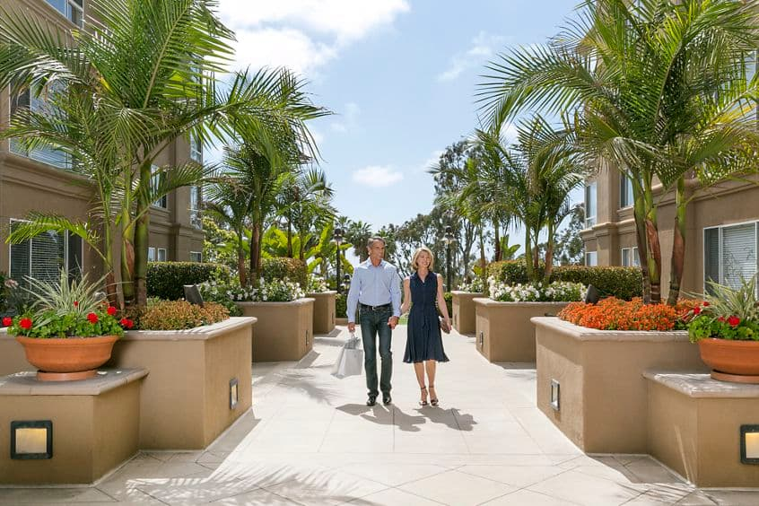 View of a couple walking through The Colony at Fashion Island Apartment Homes in Newport Beach, CA.