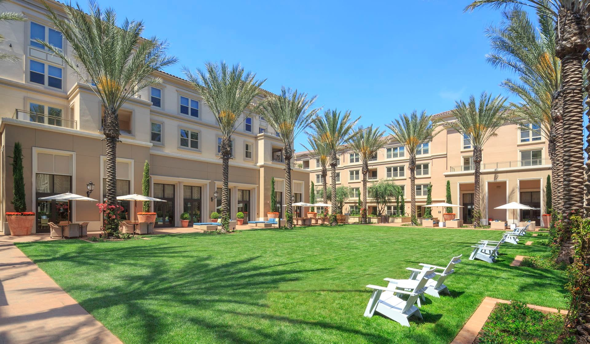 Exterior view of lawn and lounge area at Villas Fashion Island Apartment Homes in Newport Beach, CA.