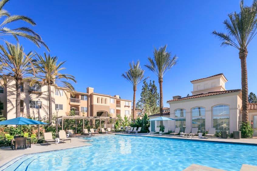 Exterior view of building and pool at Las Flores Apartment Homes in Rancho Santa Margarita, CA.