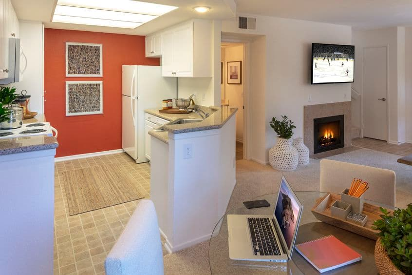 Interior view of kitchen, dining room and living room with fireplace at Rancho Maderas Apartment Homes in Tustin, CA.