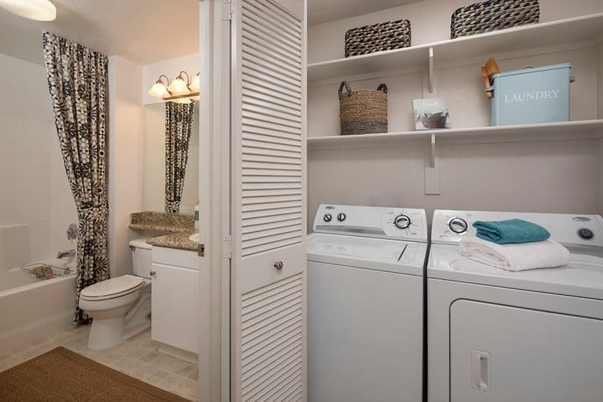 Interior view of laundry and bathroom at Rancho Santa Fe Apartment Homes in Tustin, CA.