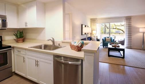 Interior view of kitchen and living room at Solazzo Apartment Homes in La Jolla, CA.