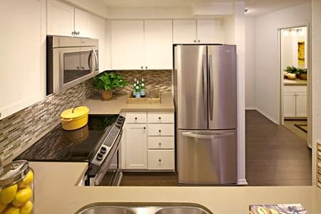Interior view of kitchen at The Village Mission Valley Apartment Homes in San Diego, CA.