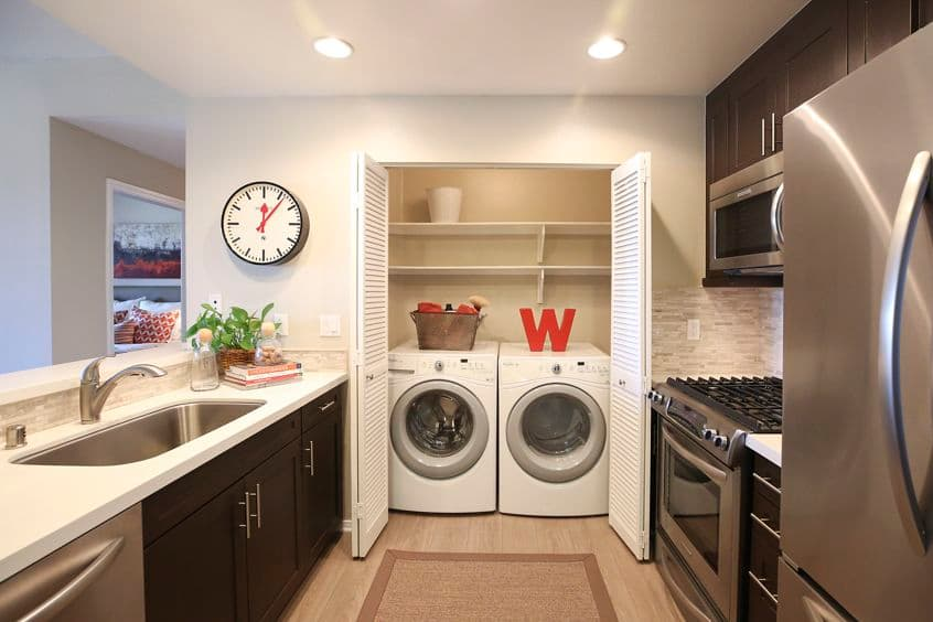 Interior view of kitchen and laundry room at The Village Mission Valley Apartment Homes in San Diego, CA.