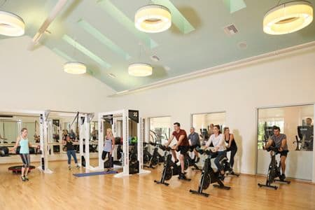 People exercising at fitness center at The Village Mission Valley Apartment Homes in Mission Valley, CA.